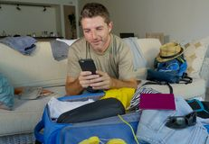 Young handsome and happy man packing travel suitcase at home sofa couch using mobile phone organizing holidays trip booking online. Smiling cheerful in summer Stock Photos