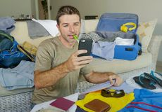 Young handsome and happy man packing travel suitcase at home sofa couch using mobile phone organizing holidays trip booking online. Smiling cheerful in summer Stock Images