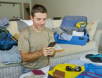 Young handsome and happy man packing travel suitcase at home sofa couch using mobile phone organizing holidays trip booking online. Smiling cheerful in summer Royalty Free Stock Photo