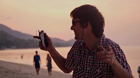 Young handsome happy man in sunglasses listen to music with mobile phone and dance on tropical beach during amazing. Young handsome man listen to music and dance stock video footage