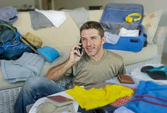 Young handsome and happy man talking with friend on mobile phone while packing travel suitcase organizing clothes and things in su. Mmer holiday trip and Stock Photo