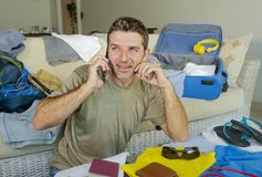 Young handsome and happy man talking with friend on mobile phone while packing travel suitcase organizing clothes and things in su. Mmer holiday trip and Royalty Free Stock Photo
