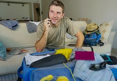 Young handsome and happy man talking with friend on mobile phone while packing travel suitcase organizing clothes and things in su. Mmer holiday trip and Royalty Free Stock Images