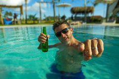 Young handsome and happy man at tropical hotel swimming pool drinking beer bottle relaxed and indulged enjoying Summer holidays. Travel in tourism and vacation stock photography