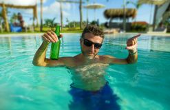 Young handsome and happy man at tropical hotel swimming pool drinking beer bottle relaxed and indulged enjoying Summer holidays. Travel in tourism and vacation royalty free stock photos
