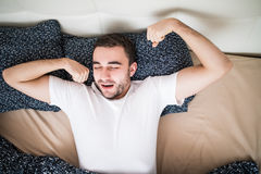 Young handsome happy man waking up on bed at home, top view. Young handsome happy man waking up on bed, top view Royalty Free Stock Images
