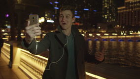 Young handsome is having a video chat near Bellagio fountain. Young man isdoing a video translation and sharing with his friends a beautiful view of Bellagio by stock video footage