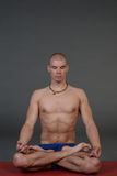 Young handsome healthy yoga man instructor doing yoga in photo studio. Stock Photos