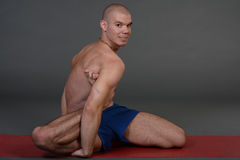 Young handsome healthy yoga man instructor doing yoga in photo studio. Royalty Free Stock Image