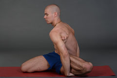 Young handsome healthy yoga man instructor doing yoga in photo studio. Royalty Free Stock Photo
