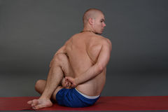 Young handsome healthy yoga man instructor doing yoga in photo studio. Royalty Free Stock Images