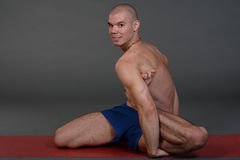 Young handsome healthy yoga man instructor doing yoga in photo studio. Royalty Free Stock Photos