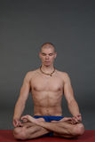 Young handsome healthy yoga man instructor doing yoga in photo studio. Royalty Free Stock Photography