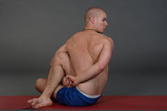 Young handsome healthy yoga man instructor doing yoga in photo studio. Stock Photography