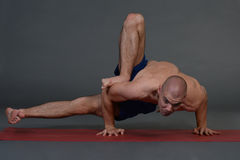 Young handsome healthy yoga man instructor doing yoga in photo studio. Stock Photo