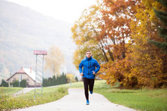 Young handsome hipster athlete running against colorful autumn n. Young handsome hipster athlete in blue sports jacket at the lake running against colorful Stock Photo
