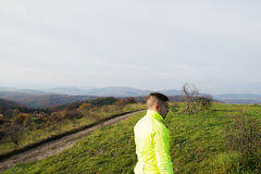 Young handsome hipster athlete running in sunny autumn nature Royalty Free Stock Photos