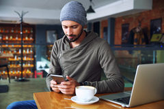 Young handsome hipster guy at the restaurant using a mobile phone. royalty free stock photography