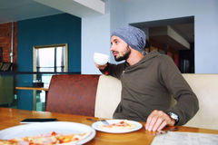 Young handsome hipster man with beard sitting in cafe talking mobile phone, holding cup of coffee. Laptop on wooden royalty free stock photos