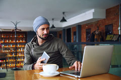 Young handsome hipster man with beard is using computer in cafeteria. Attractive male worker is using computer in cafeteria Royalty Free Stock Images