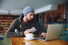 Young handsome hipster man with beard is using computer in cafeteria. Attractive male worker is using computer in cafeteria Royalty Free Stock Photo