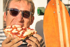 Young handsome hipster man eating a slice of pizza margherita Royalty Free Stock Photography