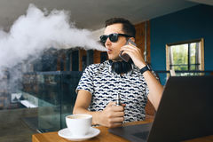 Young handsome hipster man insunglasse sitting in cafe with a cup of coffee, vaping and releases a cloud of vapor royalty free stock photos