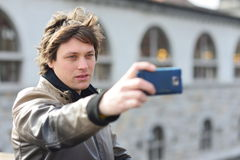 Young handsome hipster man making funny selfie Stock Image