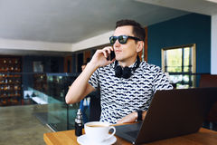 Young handsome hipster man in sunglases sitting in cafe talking mobile phone. Laptop on wooden table. royalty free stock images