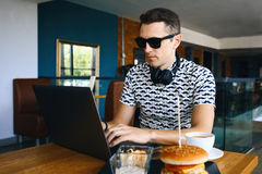 Young handsome hipster man in sunglasses is using laptop in cafeteria. Cup of coffee and cheeseburger on wooden table. stock images