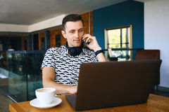Young handsome hipster man is using laptop, talking mobile phone in cafeteria. royalty free stock images