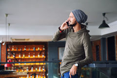 Young handsome hipster man using smartphone in cafe. Young handsome man using smartphone in cafe Royalty Free Stock Image