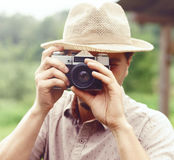 Young, handsome hipster taking pictures outdoors. Holiday, journ Royalty Free Stock Photography