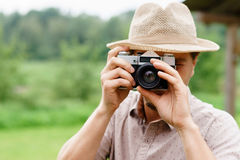 Young, handsome hipster taking pictures outdoors. Stock Photo
