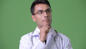 Young handsome Hispanic man doctor against green background. Studio shot of young handsome Hispanic man doctor against chroma key with green background stock video footage