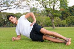Young handsome Hispanic man doing side plank at the park stock photo