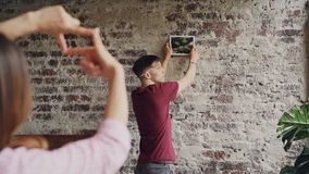Young husband is choosing place on brick wall to hang photograpt while his wife is making frame with her fingers and. Young handsome husband is choosing place on stock video