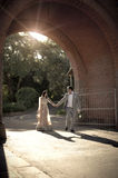 Young handsome Indian couple walking through brick archway Royalty Free Stock Image