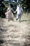 Young handsome Indian laughing couple running in field  with white roses Royalty Free Stock Image