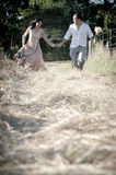 Young handsome Indian laughing couple running in field  with white roses Stock Photos