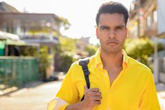 Young handsome Indian man with backpack in the streets outdoors. Portrait of young handsome Indian man in the streets outdoors royalty free stock photos