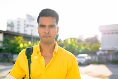Young handsome Indian man with backpack in the streets outdoors. Portrait of young handsome Indian man in the streets outdoors royalty free stock images