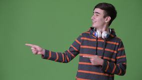 Young handsome Iranian teenage boy against green background. Studio shot of young handsome Iranian teenage boy against chroma key with green background stock video footage