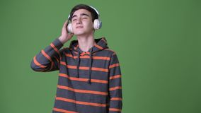 Young handsome Iranian teenage boy against green background. Studio shot of young handsome Iranian teenage boy against chroma key with green background stock video
