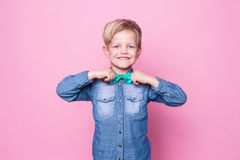 Young handsome kid smiling with blue shirt and butterfly tie. Studio portrait over pink background. Young beautiful boy with blue shirt and butterfly tie. Studio Royalty Free Stock Photos