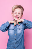Young handsome kid smiling with blue shirt and butterfly tie. Studio portrait over pink background Royalty Free Stock Image