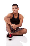 Young and handsome latin man, seated on floor Stock Photos