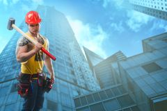 Young handsome macho man builder with muscular athletic strong body has bare torso holds hammer stock photos