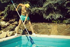 Sexy muscular man cleaning swimming pool royalty free stock photography