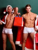 Handsome macho santa twins. Young handsome macho santa tough twins with sexy muscular athletic strong body has bare torso and strong belly in christmas cape or Royalty Free Stock Photo